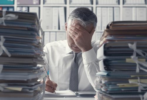 stressed businessman by Stokkete shutterstock_1051270844