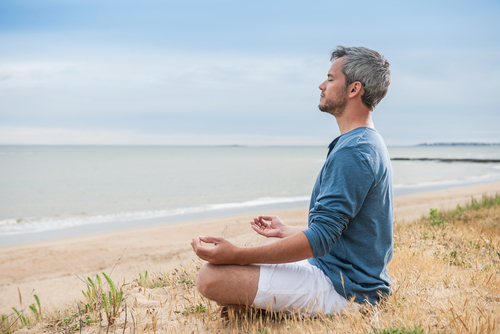 man meditating on beach by Jack Frog shutterstock_249383902